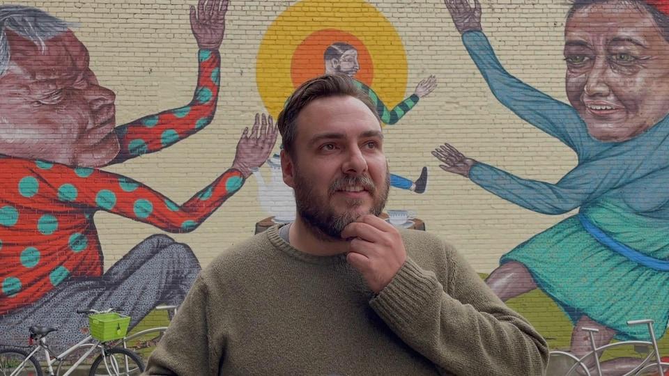 Un homme semble plongé dans ses souvenirs, derrière lui, une murale.