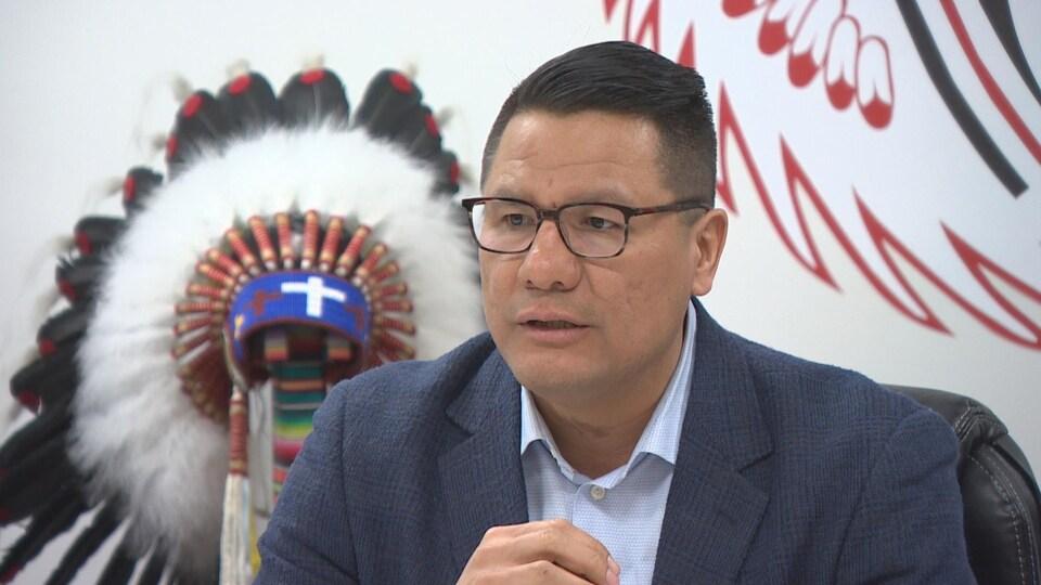 Un homme, assis dans une salle de réunion. Derrière lui, on aperçoit une coiffe autochtone posée sur un socle, et le logo de la Nation crie d'Opaskwayak.