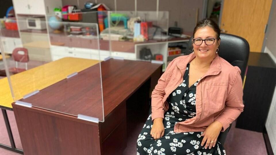 Christina Johns assise à un bureau derrière un écran de plexiglas.