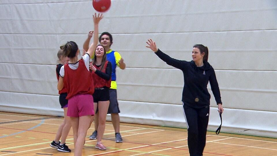 Ils jouent au ballon sous le regard de leur professeure.