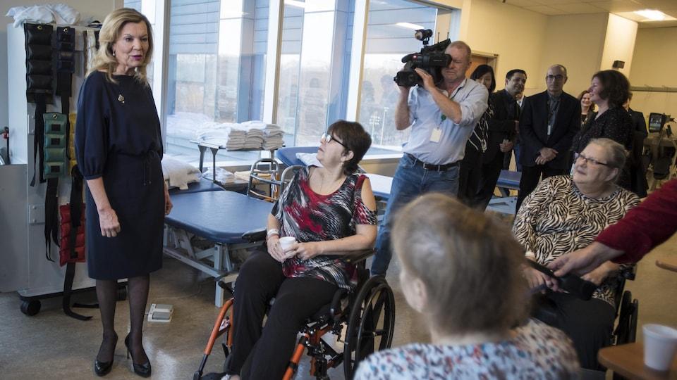 Une femme parle à des dames en fauteuil roulant alors qu'un caméraman tourne.