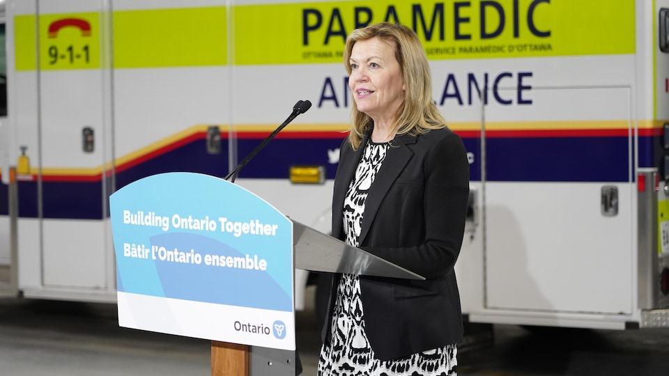 Christin Elliott derrière un lutrin lors d'un point de presse dans un garage d'ambulance.