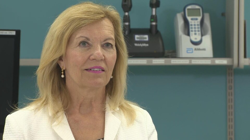 Portrait de Christine Elliott lors d'une conférence de presse dans un établissement médical.