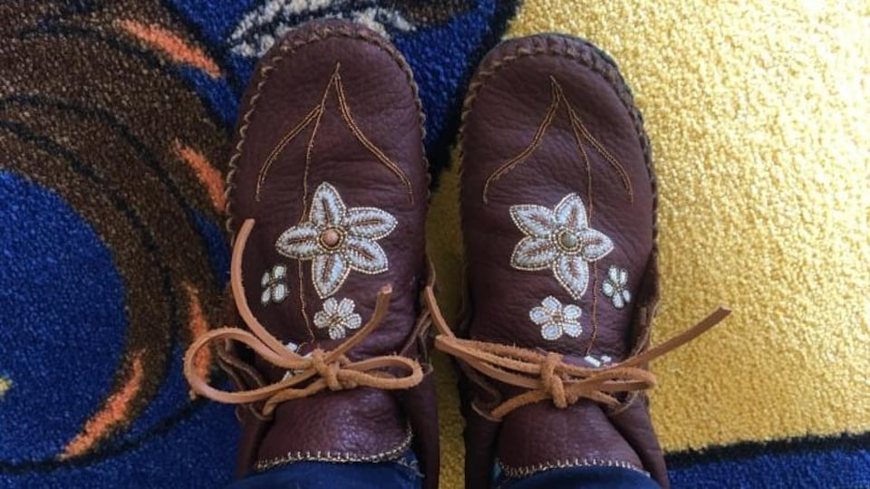 Les mocassins de Christine McRae sont bruns avec des fleurs blanches sur le dessus.