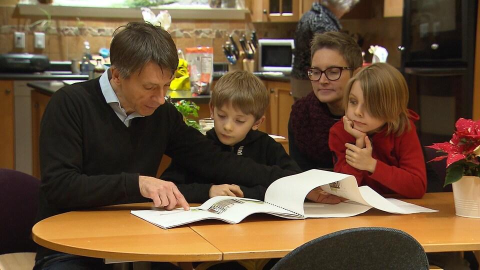Un homme, une femme et deux enfants sont assis autour d'une table et regardent des plans.