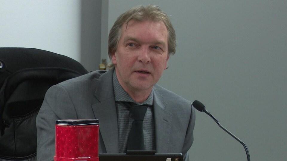 Vêtu d'un veston, le conseiller Christopher Fisher prend la parole lors d'une réunion du conseil municipal de Nipissing Ouest.