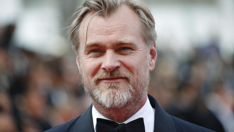 Christopher Nolan porte un costume et un noeud papillon.