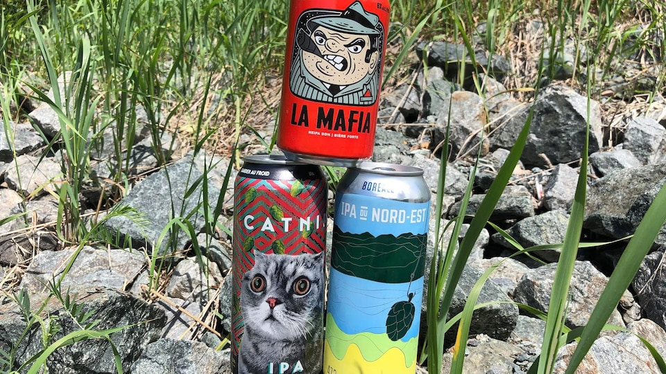 Trois canettes de bière empilées en pyramide.