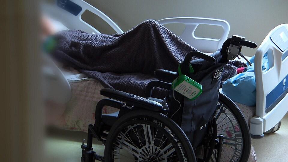 Un fauteuil roulant vide devant un lit.