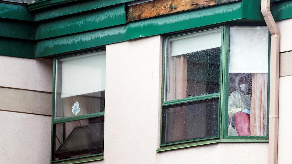 Un travailleur de la santé regarde par la fenêtre.