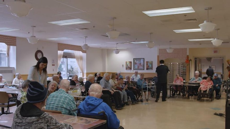 Plusieurs personnes sont réunies dans une grande salle.