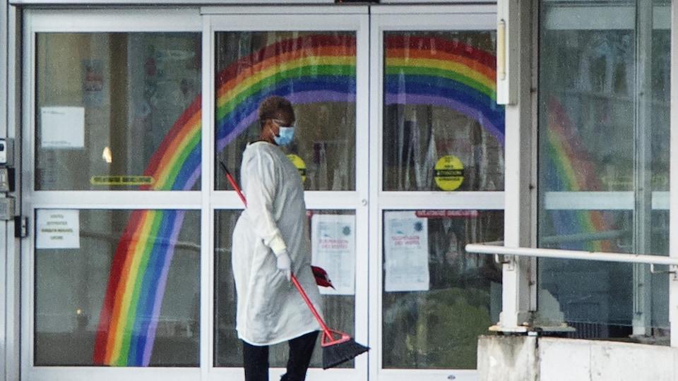 Une employée masquée passe le balai devant la porte d'entrée du CHSLD.
