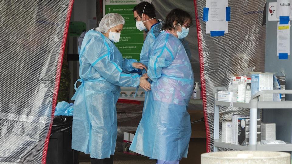 Une travailleuse attache le dos de la blouse en plastique d'une de ses consoeurs.