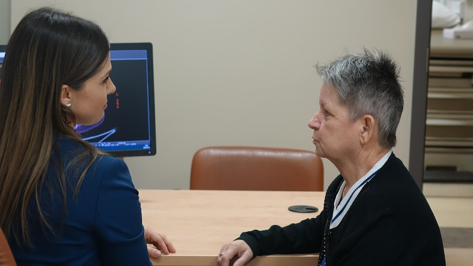 Deux femmes discutent assises devant un bureau et un ordinateur