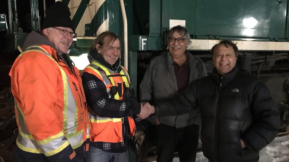 Le maire de Churchill Mike Spence avec un résident de la ville et deux opérateurs du train.