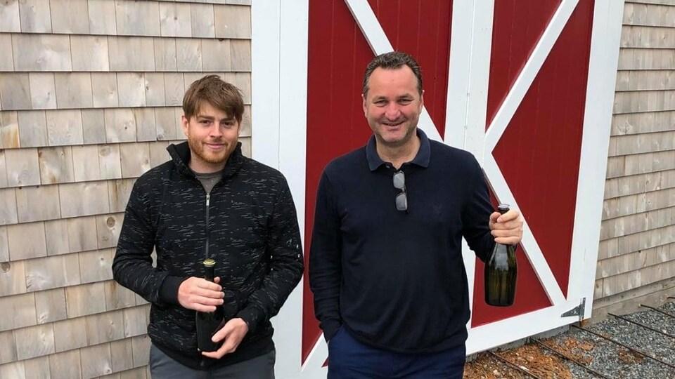 Deux personnes qui tiennent chacun une bouteille de cidre.