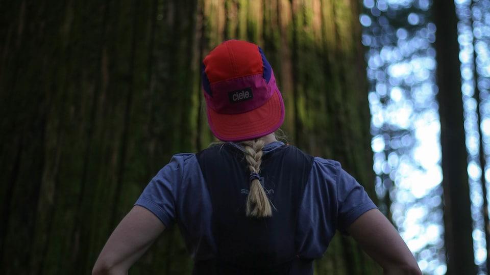 Une personne en habit de course regarde un arbre centenaire.