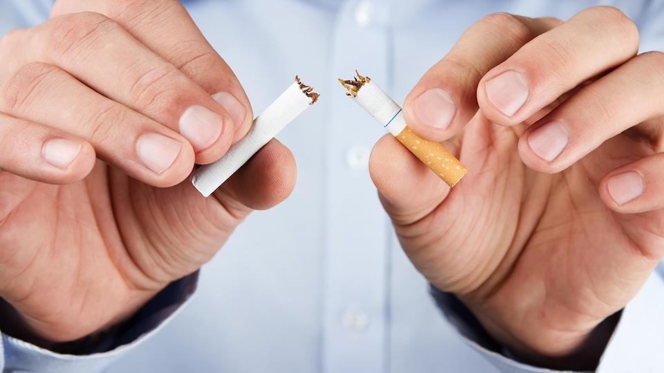 Un homme brise une cigarette en deux