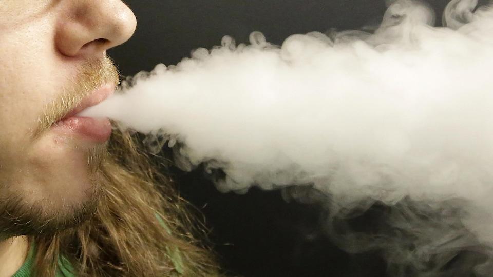 Un homme fume une cigarette électronique.