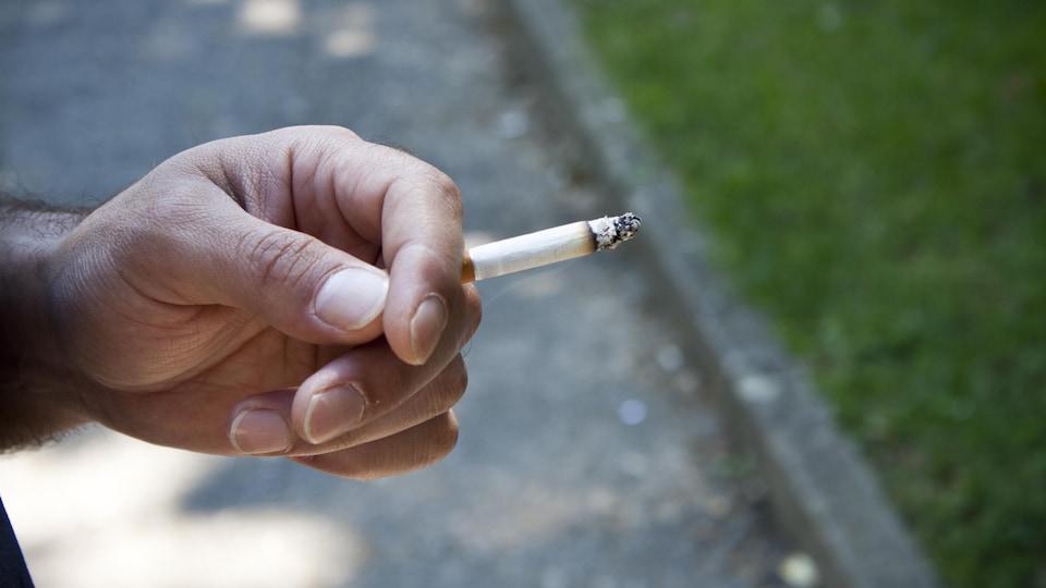 Une main tenant une cigarette allumée.