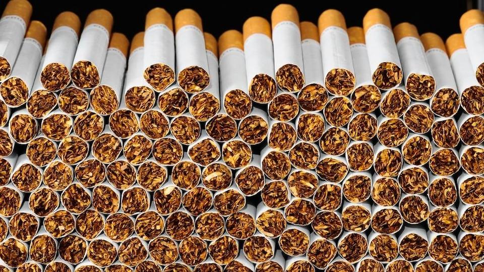 Des dizaines de cigarettes empilées les unes sur les autres.