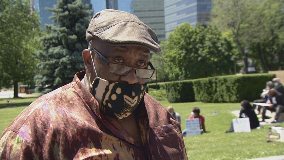 Un homme noir, petit béret, masque en tissu et lunettes