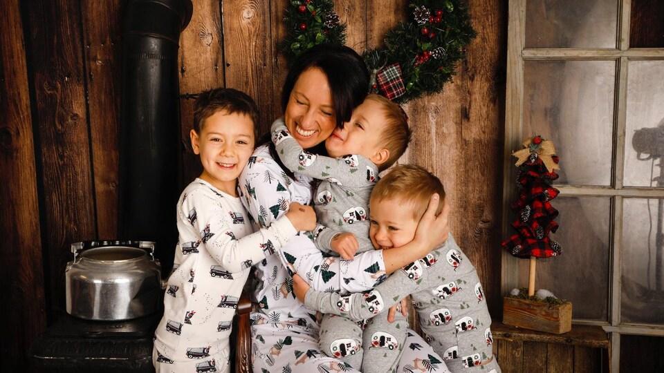 Une mère est assise près d'un poêle à bois. Un de ses enfants est sur ses genoux, deux autres sont de part et d'autre d'elle et la serrent dans leurs bras. Ils sont tous en pyjama.