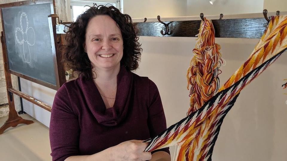 Cindy Desrochers fait une démonstration de tissage aux doigts. Elle tient entre ses doigts une ceinture qui n'est pas encore terminée et sourit.