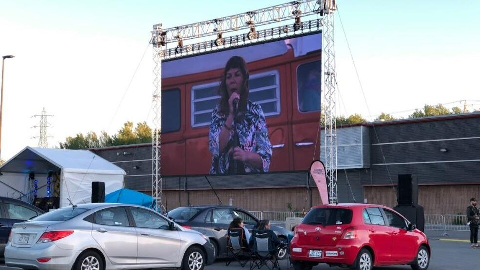 Une femme parle sur un écran géant dans un stationnement.