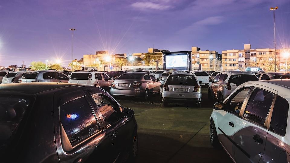 Un ciné-parc avec des voitures et un écran au fond.