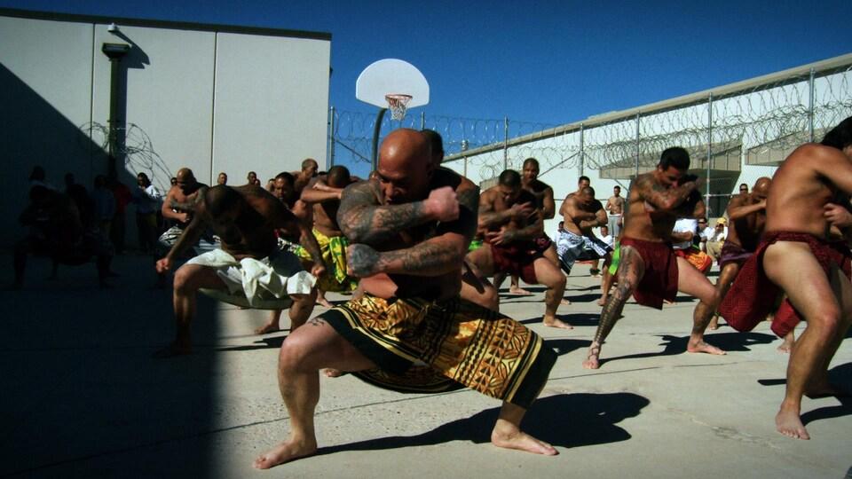 Des prisonniers en habits polynésiens pratiquent une danse traditionnelle dans une cour de prison.