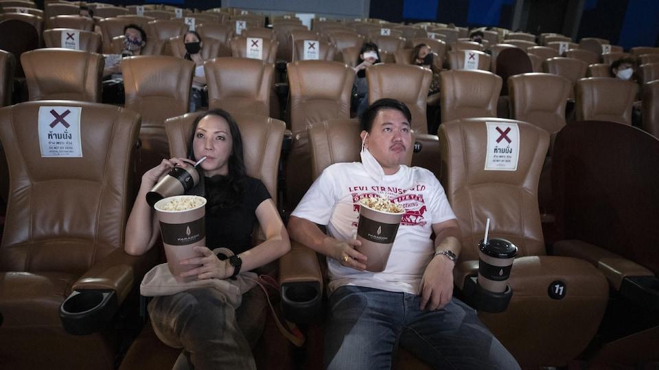 Des gens sont assis dans une salle de cinéma en respectant le principe de distanciation physique.
