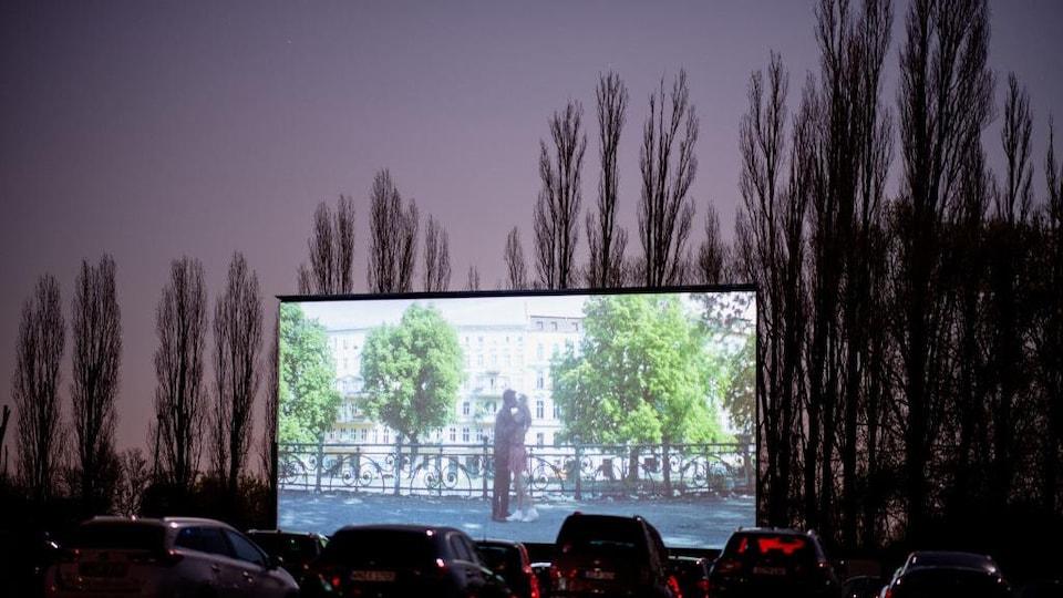 Des véhicules stationnés devant un écran géant sur lequel est projeté un film.