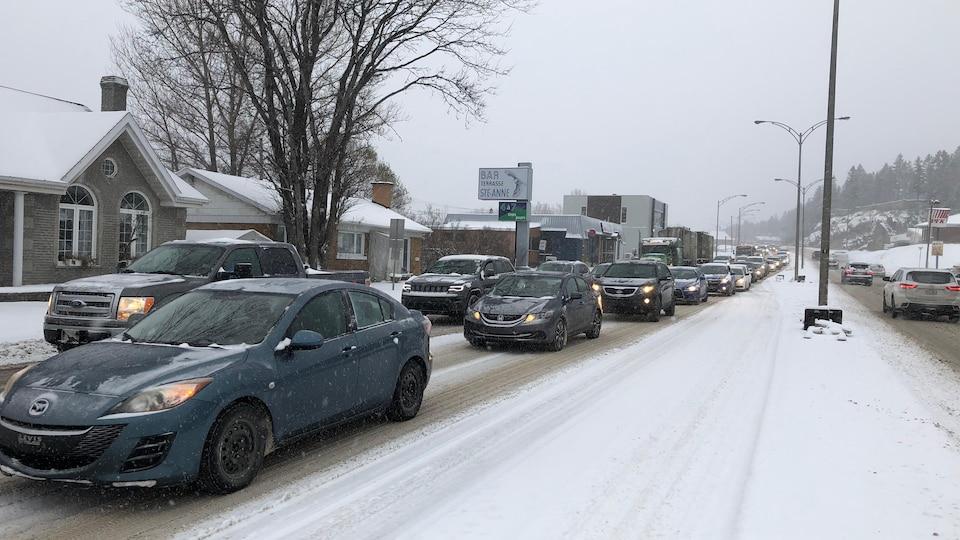 Des voitures avancent lentement sur le boulevard enneigé.