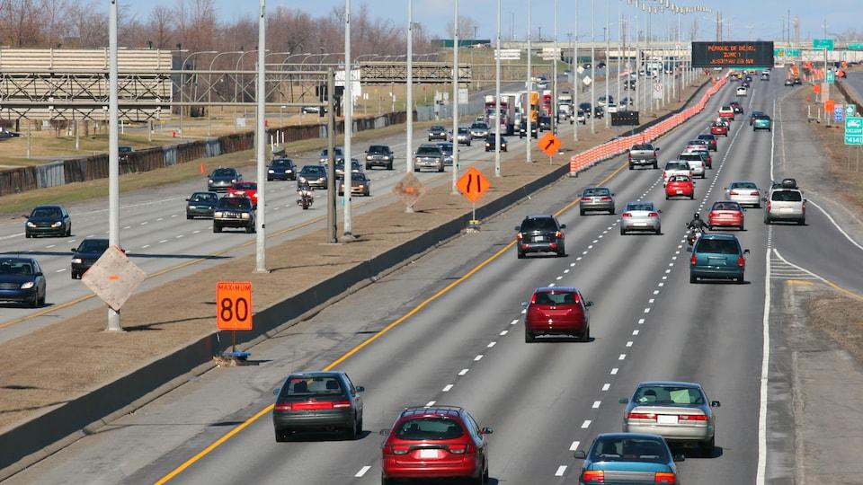 Des cônes orange bordent une autoroute.
