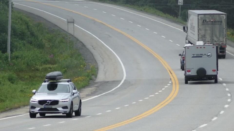 Une voiture tirant une roulotte  tente de dépasser un camion-remorque.