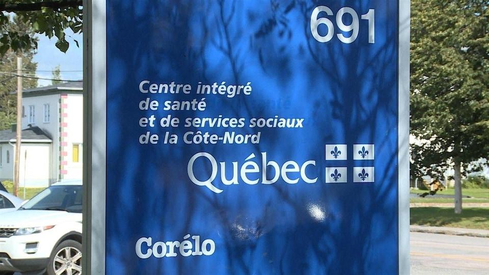 Une panneau bleu pour annoncer le Centre intégré de santé et de services sociaux de la Côte-Nord, près d'un stationnement