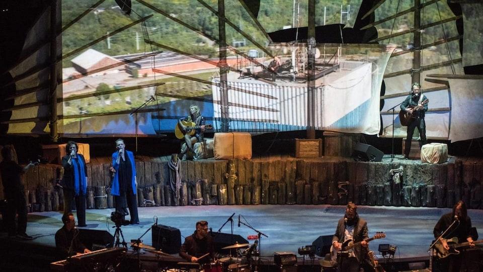 Des artistes sur scène qui chantent et des musiciens devant la scène à la scène de la Cité de l'énergie.