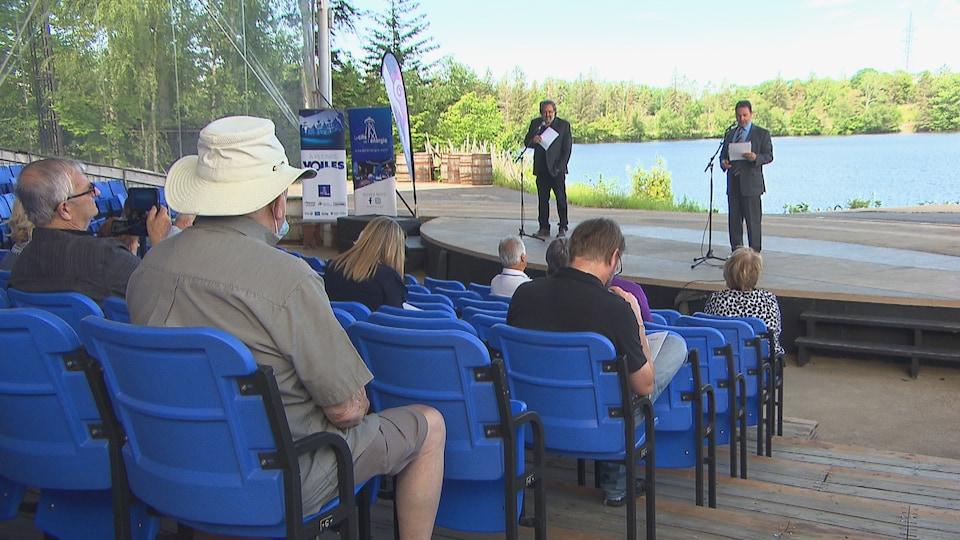 Deux personnes se tiennent devant des micros sur une scène à l'extérieur alors qu'une dizaine de personnes les écoutent.