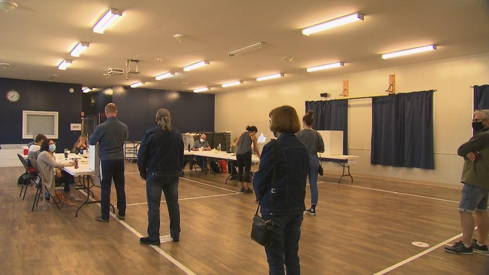 Des citoyens en file devant un bureau de vote.