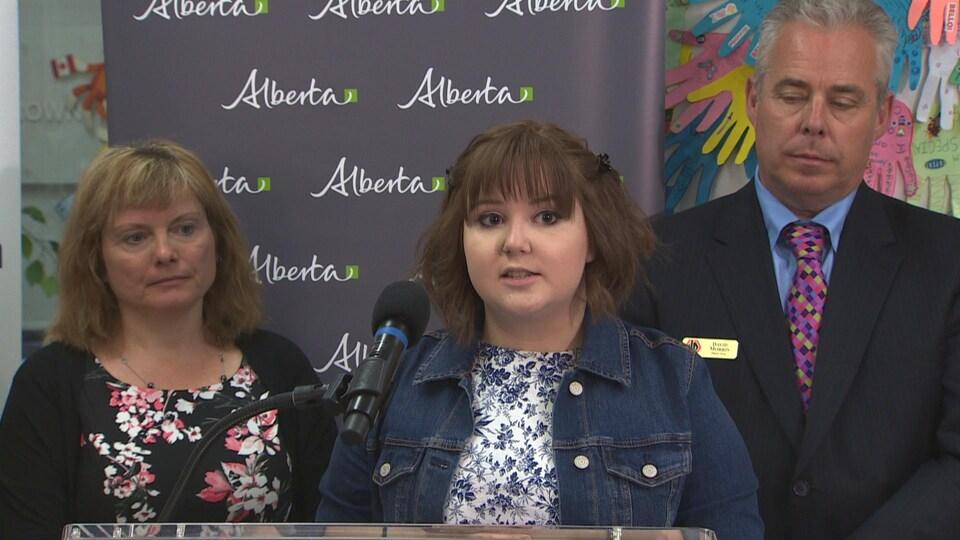 Claire Allen au centre parle au micro. Un homme se tient derrière elle à sa gauche et une femme à sa droite.