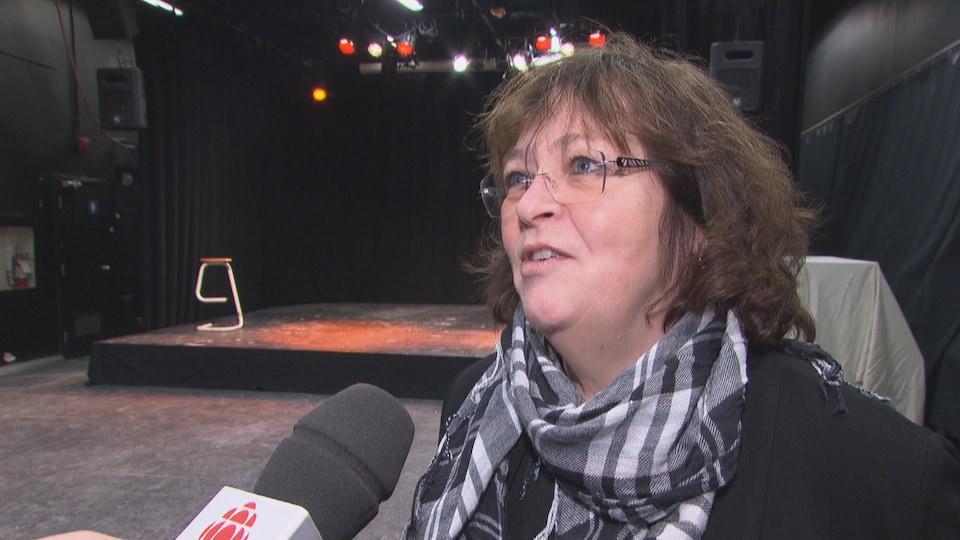 Une femme installée devant une scène est en entrevue et parle devant un micro de Radio-Canada.