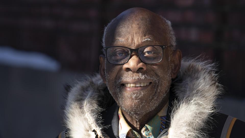 On voit Clarence Bayne, de face, qui sourit. Il est devant son domicile.