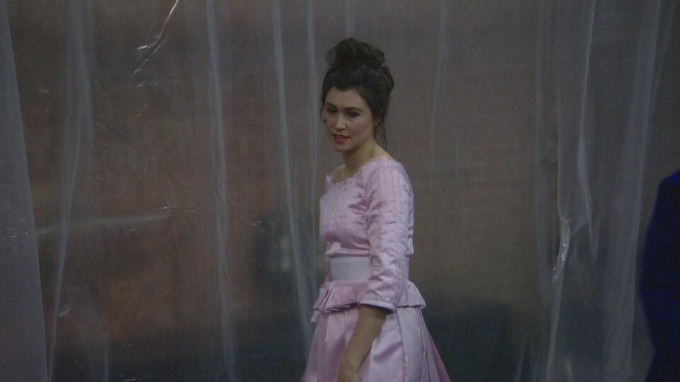 Valérie Descheneaux incarne Clarice dans la pièce. Elle porte une robe rose pâle