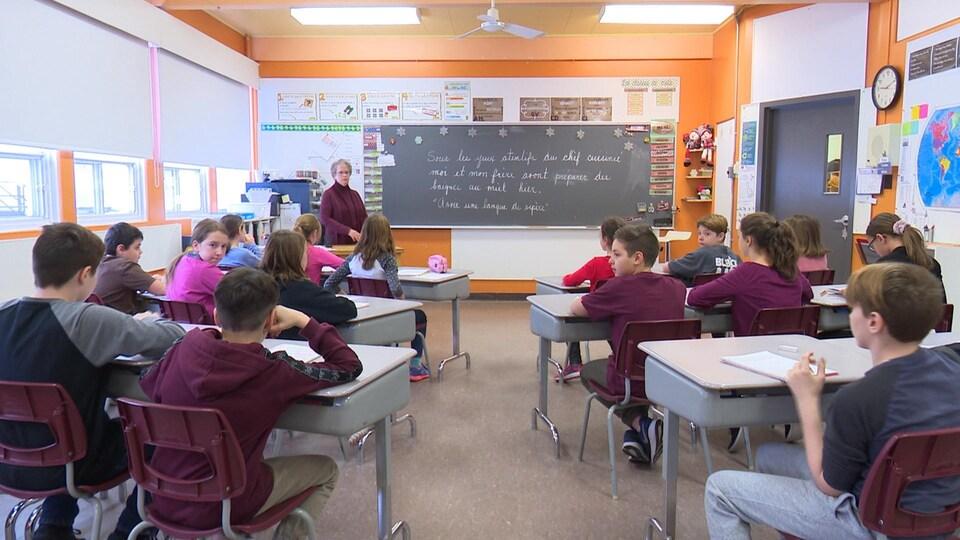 Une enseignante est devant sa classe.