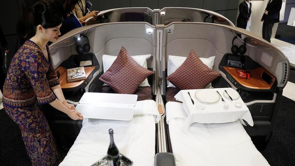 Une femme prépare une cabine de classe affaires.