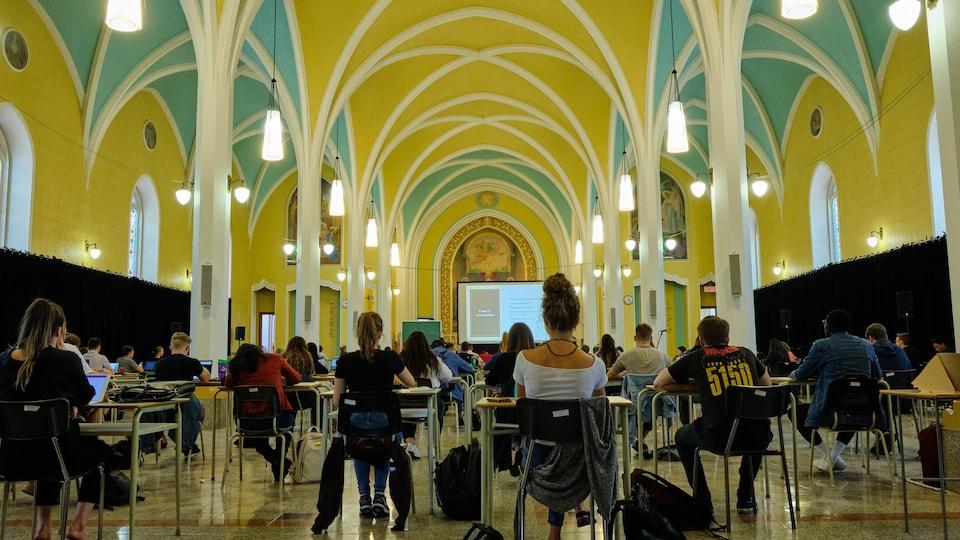 Les étudiants sont assis sur des pupitres installés dans la chapelle.