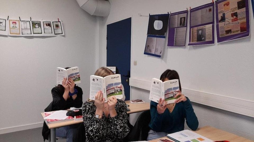 Des jeunes assis à leur pupitre montrent le livre qui cache leur visage.