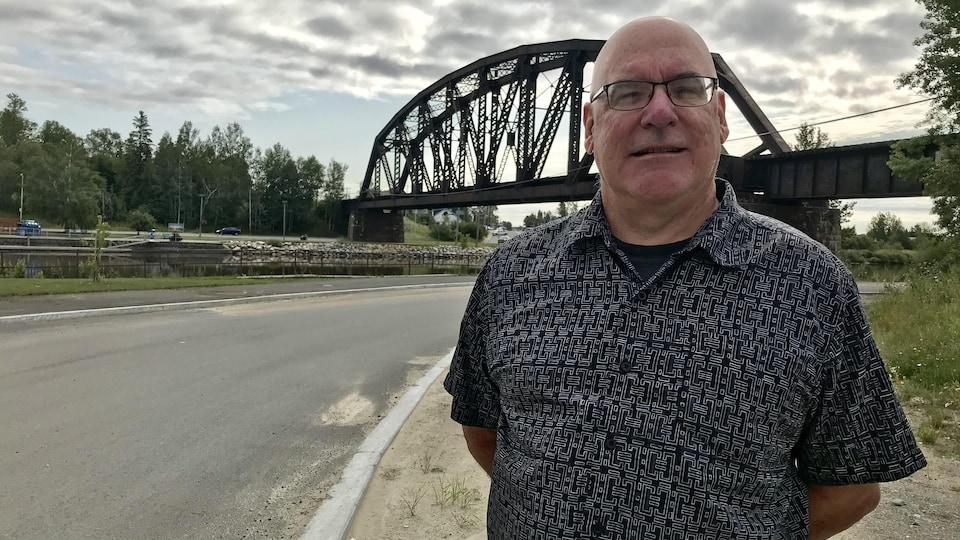 Un homme pose devant le pont de la rivière Harricana.