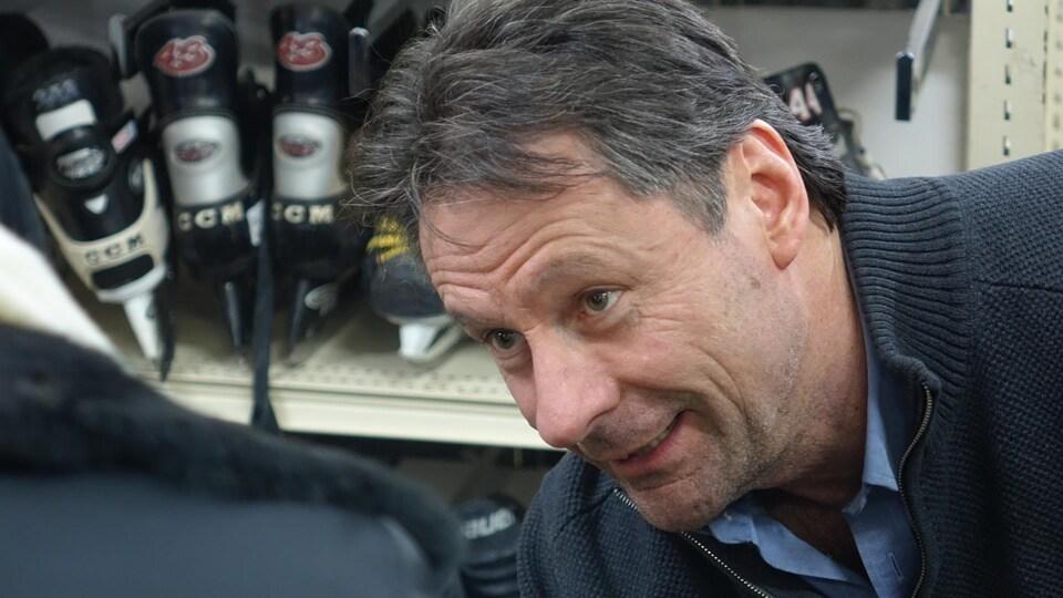 Claude Belleau, directeur général d'Estrie Aide, en train de faire essayer une paire de patins à glace à une cliente